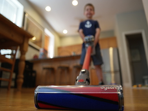 Kid cleaning with Dyson v6 Absolute cordless vacuum